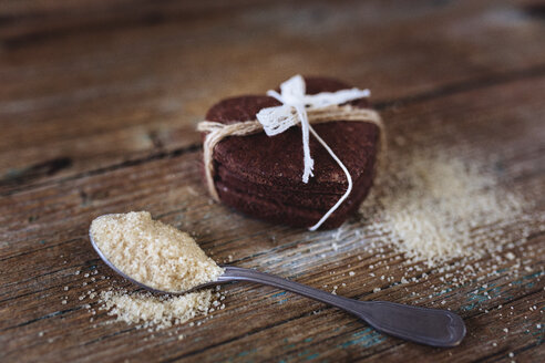 Stack of heart-shaped chocolate shortbreads tied with lace and tea spoon of brown sugar on wood - GIOF01763