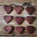 Nine heart-shaped chocolate shortbreads in rows on wood - GIOF01766