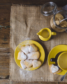 Heart-shaped shortbreads sprinkled with icing sugar on plate, cup of milk and milk pitcher on jute - GIOF01775