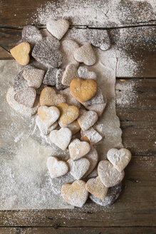 Various shortbreads sprinkled with icing sugar on paper and wood - GIOF01805