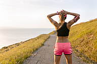 Young woman looking at the sea after workout - MGOF02888