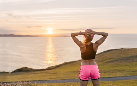 Young woman looking at the sea after workout - MGOF02900