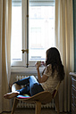 Woman with cup of coffee sitting on chair at home looking through window - KKAF00361