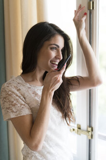 Woman speaking on the phone while looking through window - KKAF00373