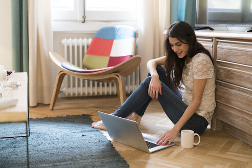 Young woman sitting on the floor at home using laptop - KKAF00379