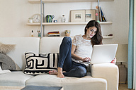 Woman sitting on couch at home using laptop - KKAF00385