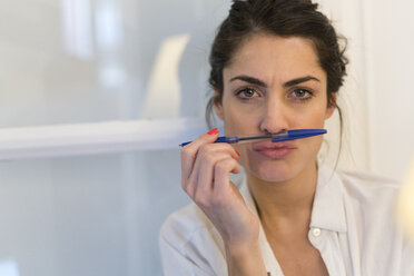 Portrait of woman with ballpen pouting mouth - KKAF00394