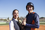 Portrait of smiling male and female baseball player - ABZF01894