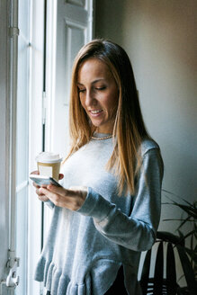 Young woman at the window holding cell phone and takeaway coffee - VABF01099