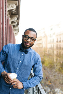 Portrait of smiling young man on balcony with takeaway coffee - VABF01105