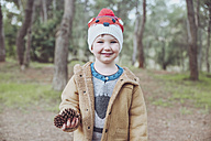 Portrait of boy wearing wooly hat holding pine cones in forest - RTBF00628
