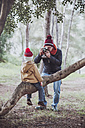 Father taking a picture of his son sitting on tree trunk in forest - RTBF00634