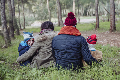 Rear view of family sitting in forest - RTBF00643