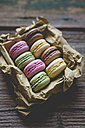 Different macarons in a box on wood - GIOF01813