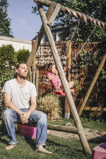 Exhausted father in garden with daughter on swing - JOSF00483