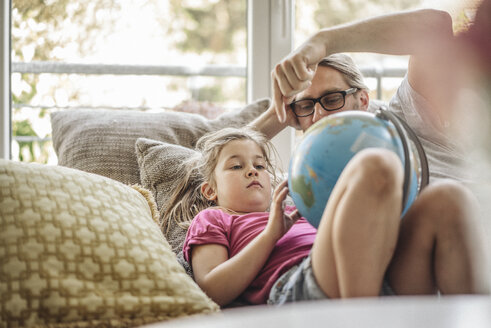 Father and daughter lying with globe on sofa - JOSF00486