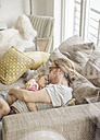 Father relaxing with daughter on sofa - JOSF00489