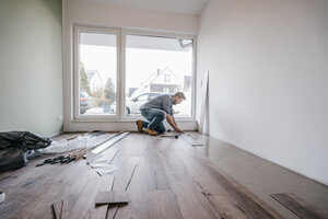 Mature man fitting flooring in new home - JOSF00491