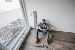 Mature man fitting flooring in new home, drinking coffee and taking a break - JOSF00494