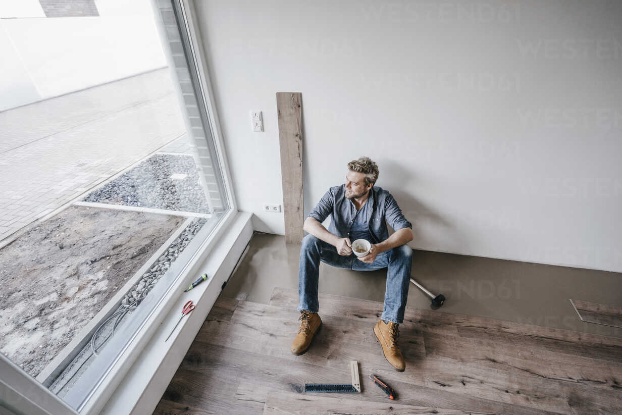Mature man fitting flooring in new home, drinking coffee and taking a break - JOSF00494 - Joseffson/Westend61