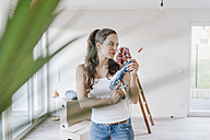 Mature woman moving house holding glue gun - JOSF00497