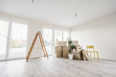 Moving boxes and ladder in empty room of a new home - JOSF00500