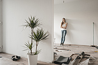 Mature woman moving house, leaning against wall - JOSF00506