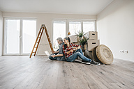Couple sitting on floor of their new home among moving boxes - JOSF00509