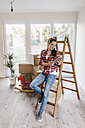 Mature woman moving house, leaning against ladder, using tablet - JOSF00518