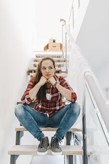 Mature woman moving house, sitting on stairs - JOSF00524