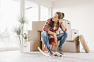Mature woman moving house, sitting on rocking horse - JOSF00527