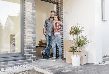 Happy couple standing in door of their new home - JOSF00533