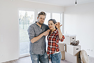 Couple moving house, woman holding keys of new home - JOSF00539