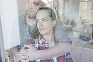 Couple standing at window of their new home - JOSF00545