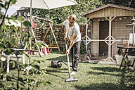 Man hoovering lawn in garden - JOSF00566