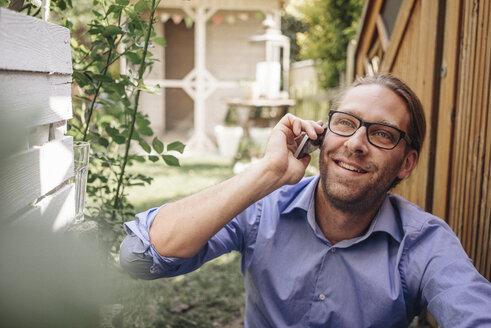 Man on the phone in garden - JOSF00569