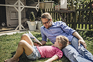 Father reading book with daughter in garden - JOSF00575