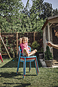 Father taking cell phone picture of daughter sitting on chair in garden - JOSF00578