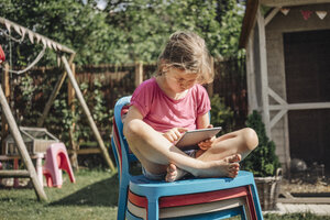 Girl sitting on stack of chairs in garden using tablet - JOSF00581