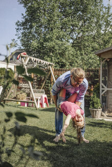 Father playing with daughter in garden - JOSF00584