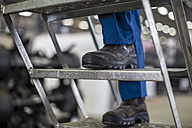 Factory worker standing on ladder, close up - ZEF12761