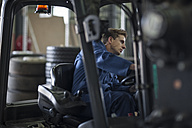 Factory working driving a fork lift in warehouse - ZEF12773