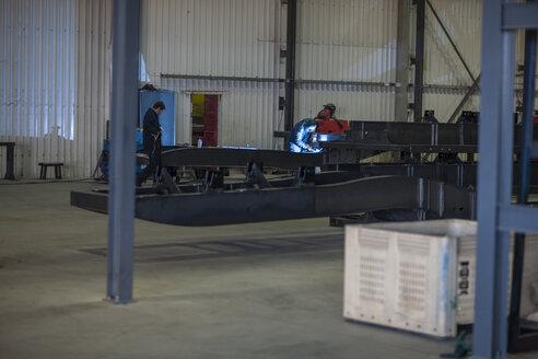 Factory worker in truck manufacture welding steel parts - ZEF12776