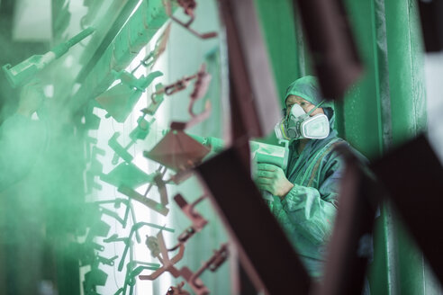 Painters spraying steel components in spray booth of a factory - ZEF12779