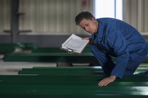 Factory worker in truck manufacture inspecting steel parts - ZEF12782