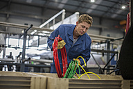 Factory worker in truck manufacture sorting cables in to box - ZEF12794
