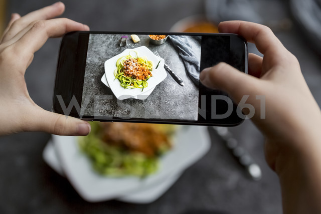 Girl taking a photo zoodles with vegetarian bolognese sauce with her smartphone, close-up - SARF03176