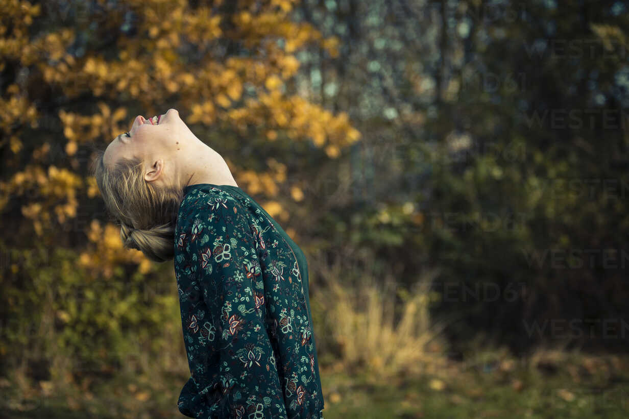 Blond young woman standing with head back in autumnal forest - NGF00389 - Nadine Ginzel/Westend61