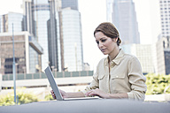 Businesswoman using laptop outdoors - WESTF22588
