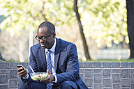 Businessman using cell phone during lunch break - WESTF22600